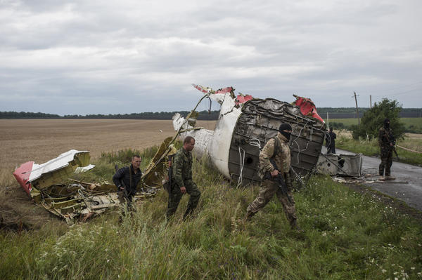 Pro-Russian fighters at the crash site of a Malaysia Airlines passenger jet near the village of Hrabove, Ukraine on Friday. One day after the downing of the jetliner, investigators are trying to learn more about the crash and who might be responsible. The passenger jet had nearly 300 people onboard; none survived.