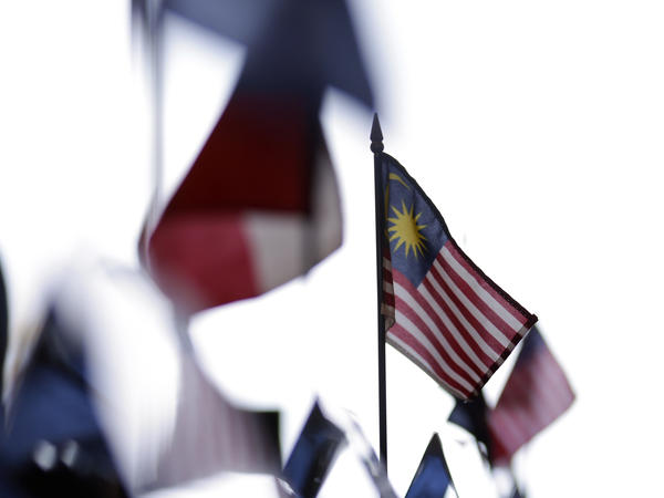 A Malaysian flag sits on a table among other flags during a news conference at the Trans-Pacific Partnership Free Trade Agreement talks in July 2012 in San Diego. Nearly two and a half years later, the deal remains incomplete.