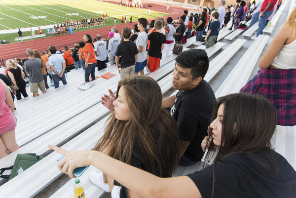 Jose and his friends Giovana Flores (left) and Anahi Macias sit and wait for the first home football game of the season to kickoff at S.E. Williams Stadium in Tulsa, Okla. All three students recently started their freshman year at Booker T. Washington High School.