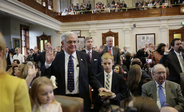 Casey Smith (center) holds a family Bible as his grandfather, Texas state Rep. Jimmie Don Aycock, R-Killeen, takes the oath of office with his fellow legislators on Jan. 13, 2015, in Austin.