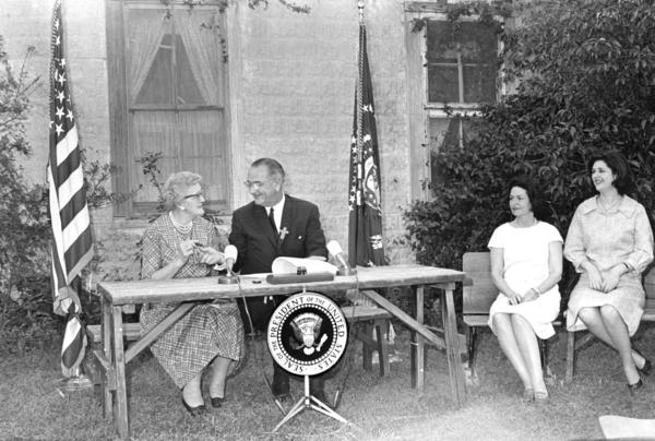 President Lyndon B. Johnson jokes with his first-grade teacher, Kate Deadrich Loney, after signing the Elementary and Secondary Education Act near Stonewall, Texas, on April 11, 1965. Seated at right are first lady Ladybird Johnson and daughter Lynda Bird.