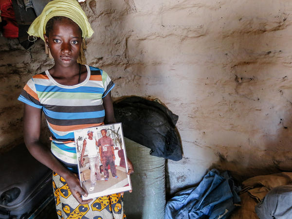 Nialina Ba holds the only picture she has of her late husband, Bourang Ba (in the white shirt).