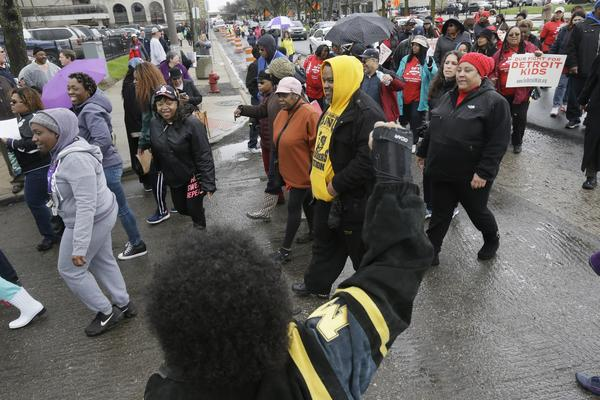 Detroit teachers march outside the district headquarters on Monday. Nearly all of Detroit's public schools were also closed on Tuesday as teachers protest a funding gap that could mean lost paychecks.