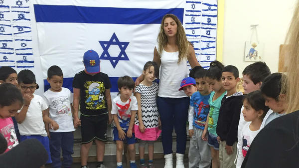 A kindergarten teacher in Jerusalem stands with students as they listen to sirens that played nationwide on Thursday to commemorate Holocaust Remembrance Day. This year, a new national Holocaust curriculum is being fully implemented in kindergarten.