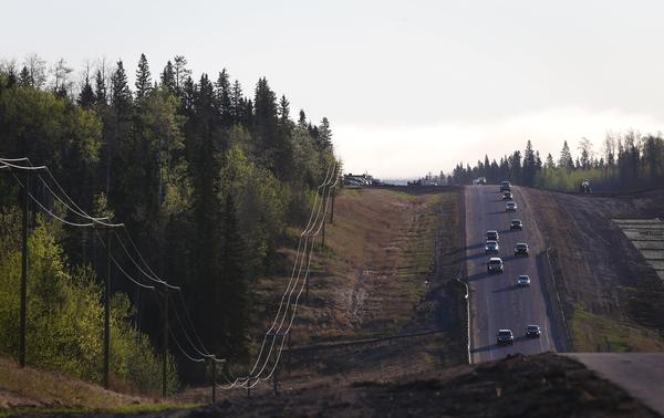 A convoy of cars sporadically heads south on Highway 63 on Friday after evacuees were stranded at an oil sands camp north of Fort McMurray.