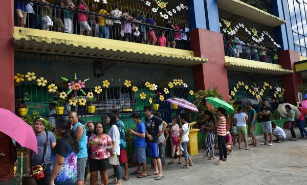 People line up to cast their ballots in the presidential election in suburban Manila.