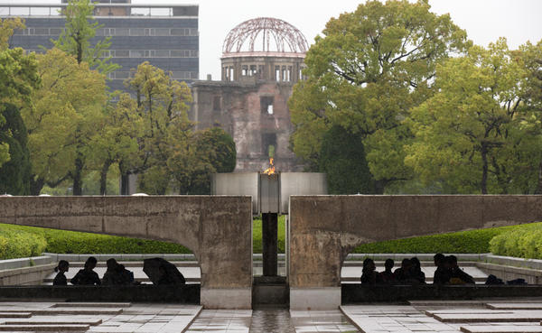 Visitors shelter from the rain under the Peace Flame as they visit the Memorial Park and the nearby Hiroshima Peace Memorial Museum on April 21 in Hiroshima, Japan. The dome in the background was destroyed during the attack, and preserved as a monument. The park, museum and dome are dedicated to the victims of the world's first nuclear attack, and to the pursuit of peace.