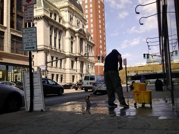 A man cleans up the streets near City Hall