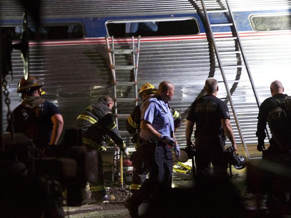 Emergency workers search for injured passengers after an Amtrak train carrying more than 230 from Washington to New York derailed in May 2015.