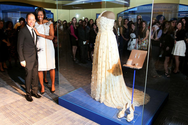 The First Lady and fashion designer Jason Wu stand next to the gown she wore to the inaugural balls at the Smithsonian Museum of American History on March 9, 2010 in Washington, D.C. Mrs. Obama continues a long tradition of first ladies who have donated their inaugural gown to be on display at the Smithsonian.