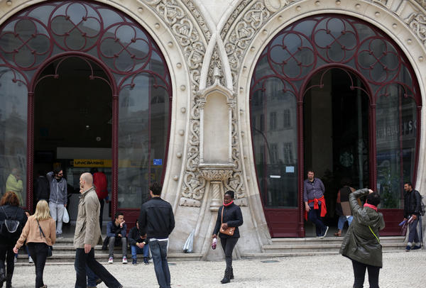 A woman takes pictures by the front doors of Lisbon's Rossio train station on Thursday. A statue of 16th century King Sebastian, around 3-feet tall, stood in the now empty niche between the doors.