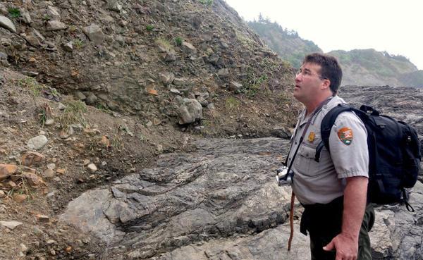<p>Redwood National Park Archeologist Michael Peterson surveys the erosion at a former Tolowa village site along the California coast.</p>