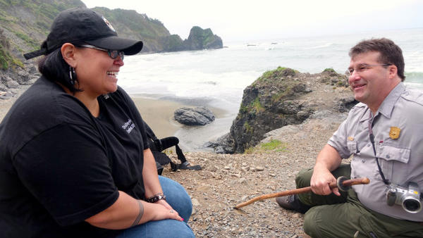 <p>Smith River Rancheria Tribal Heritage Preservation Officer Suntayea Steinruck and RWNP Archeologist Michael Peterson talk on an eroding spit of land.</p>