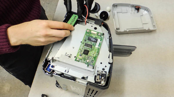<p>A Basel Action Network employee places a GPS tracker inside a broken printer.</p>