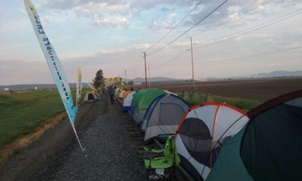 <p>More than 100 people have been camped out on the rail lines leading to a pair of oil refineries in Washington since Friday. Sunday morning, officials arrested 52 of the protestors.</p>