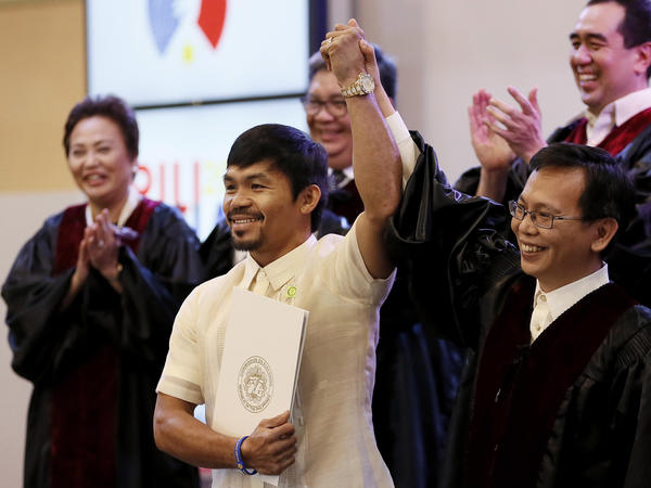 Filipino boxing great Manny Pacquiao holds his Certificate of Canvass as he is proclaimed the seventh senator by Commissioner Christopher Lim (right) in a ceremony Thursday.