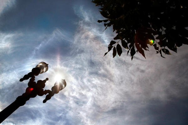 <p>Incoming high clouds swirl overhead as the summer sun breaks through behind a street lamp in Portland, Oregon.</p>