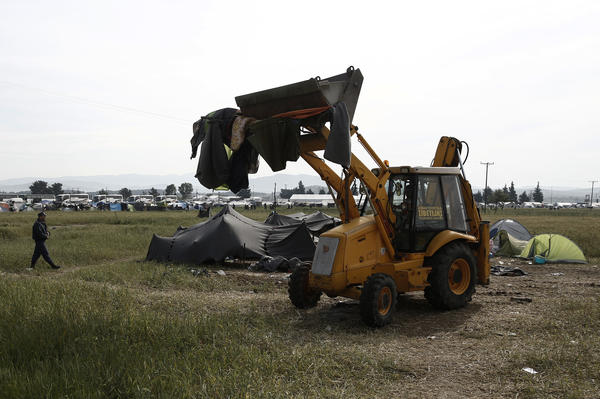An excavator collects tents from the makeshift migrant camp near the village of Idomeni, Greece, on Tuesday.
