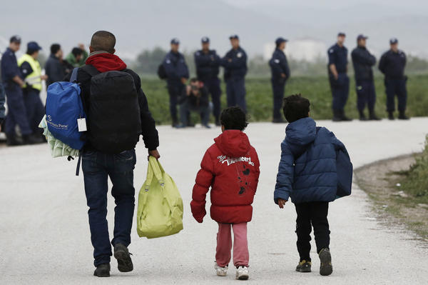 A migrant and children carry their belongings at the Idomeni camp on Tuesday. In an operation that began shortly after sunrise, hundreds of Greek police began evacuating the sprawling camp.
