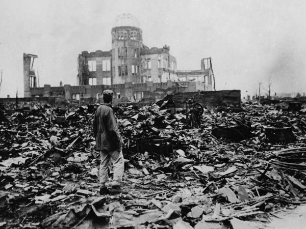 One month after the atomic bomb was dropped on Hiroshima, a correspondent stands amid ruins left by the explosion. The structure seen standing became the Hiroshima Peace Memorial, which President Obama will visit Friday.