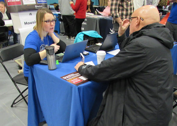 Dawn Barrett works with a veteran inquiring about housing at the Seattle Stand Down.