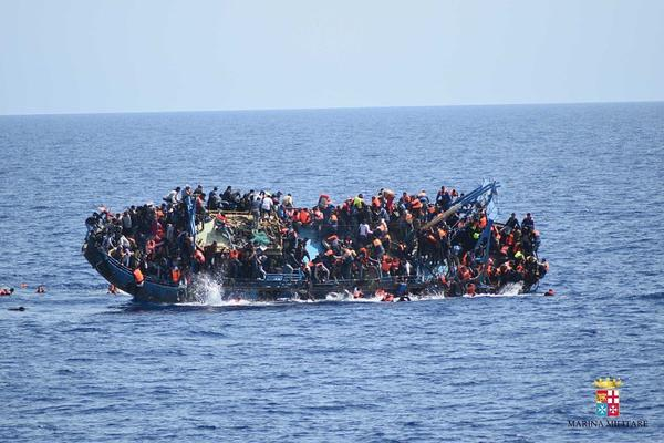 Migrants in an overcrowded boat, which was about to capsize, are rescued by Bettica and Bergamini ships of the Italian navy at Sicilian Strait, between Libya and Italy, in the Mediterranean Sea on Wednesday.