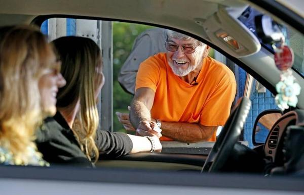 Toll collector John Struckman takes the $1 toll from travelers in the late day at the toll plaza on Card Sound Road. The toll plaza, an alternative route to the Florida Keys, is one of the last remaining manned toll facilities in South Florida. (Charles Trainor Jr. /Miami Herald)