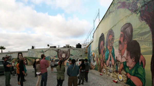Turista Libre's street art tour takes people around Tijuana to check out the city's murals. Mexican muralists Glow and El Norteno accompanied the group and spoke about their pieces. (In this photo, Norteno's work is on the right and Glow's is on the left.)