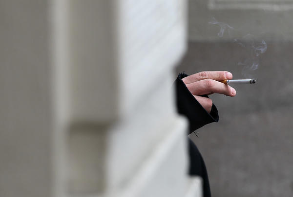 A smoker in San Francisco holds a cigarette. If Gov. Jerry Brown signs the bill, California will become the second state to raise the age limit for buying tobacco products from 18 to 21.