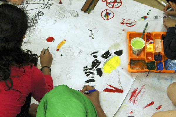 Students sketch, paint and write out their ideas on one large sheet of paper.
