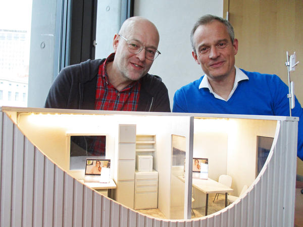 Harald Neidhardt (left) and Mirko Bass, shown here with a model of their mobile medical clinic, had been volunteering to help asylum seekers in Hamburg but wanted to do more. The clinic they created from a refurbished shipping container received more than 3,000 patients between November and the end of April.