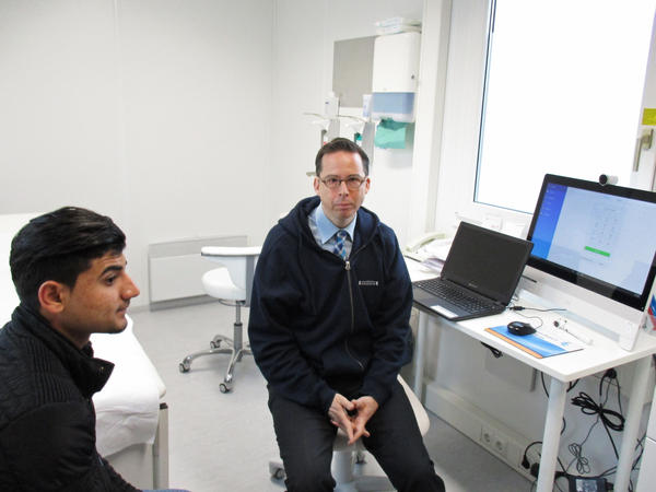 Iraqi asylum seeker Maher Murad (left) sought help from Dr. Martin Scherer for a sore throat. In the exam room, Scherer worked online with an Arabic-speaking translator.