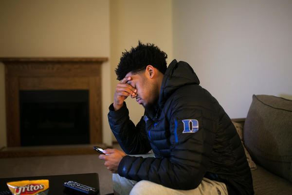 Cook rests his eyes while texting with friends before watching the Feb. 17 basketball game between Duke and archrival UNC on TV at the rental home he shares with a teammate in Canton.