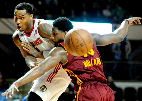 Coty Clarke of the Maine Red Claws makes a pass around John Holland of the Canton Charge in the first round of the D-League Eastern Conference playoffs at the Cross Insurance Arena in Portland, Maine, on April 7.