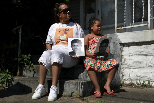People wait in front of their home for the funeral procession of Muhammad Ali to pass by.