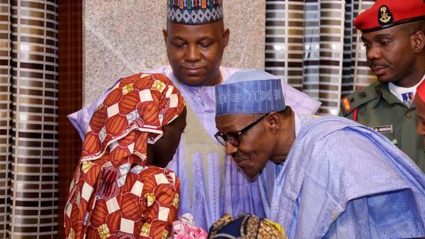 Nigerian president Muhammadu Buhari speaks with freed Chibok schoolgirl Amina Ali Nkeki, who is carrying her baby, as Borno state governor Kashim Shettima (C) looks on in Abuja, on May 19, 2016.