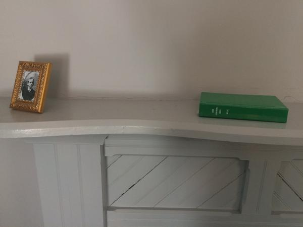 A picutre of Ben and a copy of Look Homeward Angel sit on the mantel of the room died in.