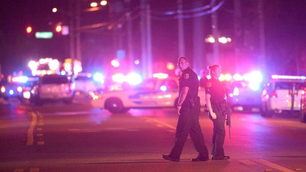 Police officers stand guard down the street from the scene of a deadly mass shooting at the Pulse Orlando nightclub in Orlando, Fla., early in the morning on Sunday. Authorities say at least 50 people died in the attack.