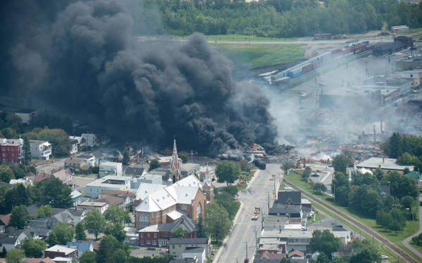 <p>Smoke rises from railway cars that were carrying crude oil after derailing in downtown Lac Megantic, Quebec, Canada, July 6, 2013. A large swath of Lac Megantic was destroyed after a train carrying crude oil derailed, sparking several explosions and forcing the evacuation of up to 1,000 people.</p>