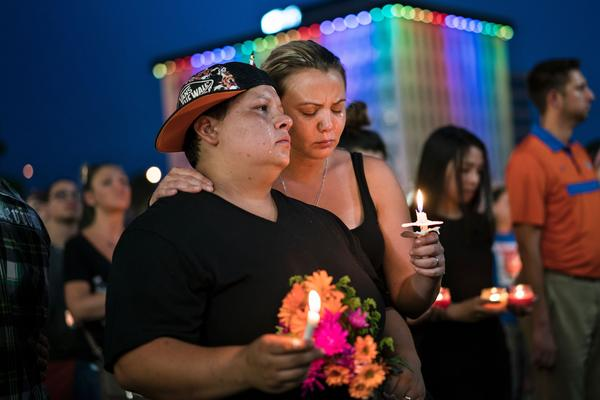 Nicole Edwards and her wife, Kellie Edwards, observe a moment of silence Monday during a vigil in Orlando, Fla., for victims of the mass shooting at the Pulse Orlando nightclub on Sunday.