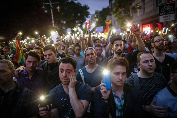 """People hold candles and lights during a vigil outside the Stonewall Inn. New York Gov. Andrew Cuomo joined the vigil and delivered a full-throated demand for what he called """"sensible gun control."""""""