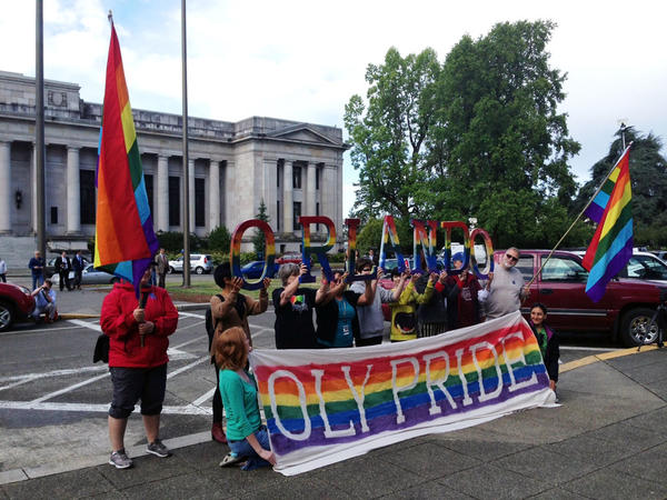 Members of Olympia's LGBT community hold up letters spelling ORLANDO at a flag raising event at the Washington state Capitol.