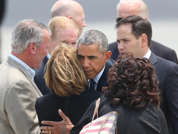 President Obama hugs Orange County Mayor Teresa Jacobs as Orlando Mayor Buddy Dyer (left) watches, at Orlando International Airport on Thursday.