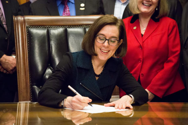 <p>Oregon Gov. Kate Brown signs a bill into law to increase the state minimum wage in March 2016.</p>