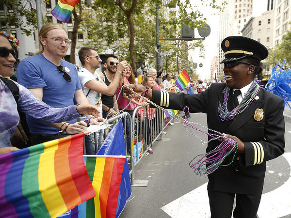 San Francisco Fire Department Deputy Chief Raemona Williams (right) passes out beaded necklaces to the crowd during the 2015 San Francisco Gay Pride Parade.