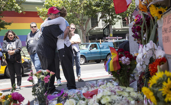 Larry Pascua hugs a friend Monday in San Francisco amid flowers and other items left as a memorial to those killed in the attack on a gay nightclub in Orlando, Fla.