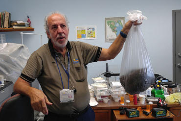 At the Broward County Mosquito Control office in Pembroke Pines, Florida, biologist Evaristo Miqueli holds a bag of thousands of dead mosquitoes his agency has caught in 2016.