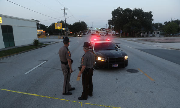 Law enforcement officials block off the road near Pulse nightclub on June 15 as they continue the investigation into the shooting there. The Justice Department on Monday released a transcript of a 911 call that Omar Mateen made the night of the shooting.