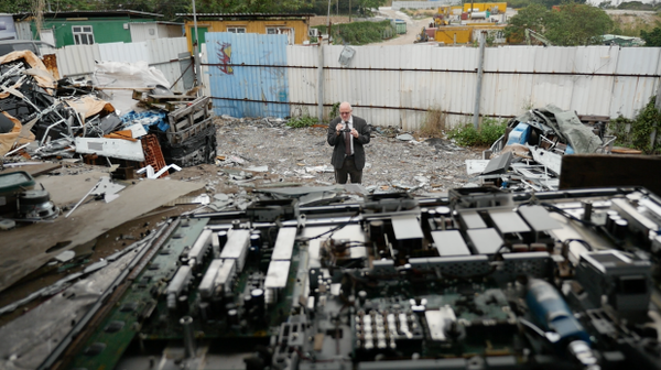 <p>Jim Puckett, executive director of the Basel Action Network, surveys an e-waste junkyard in the New Territories region of Hong Kong. In the foreground, an LCD monitor is dismantled.</p>
