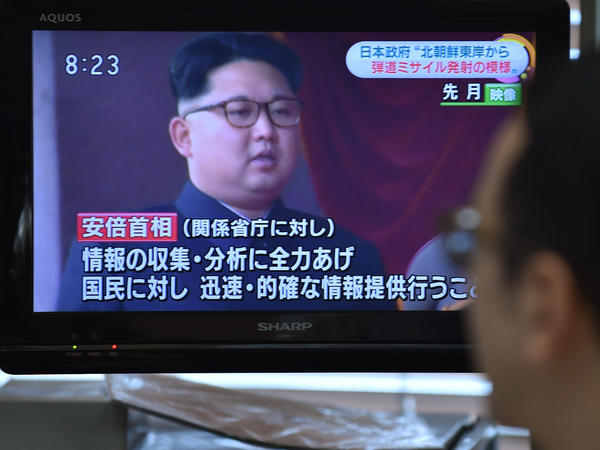 A man looks at a television reporting on North Korea's missile launching in Tokyo. North Korea test-fired what appeared to be two medium-range Musudan missiles in quick succession.